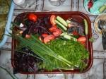 Salat- und Kräuterplatte als Beilage zu fleischlastigem Essen in der Ukraine